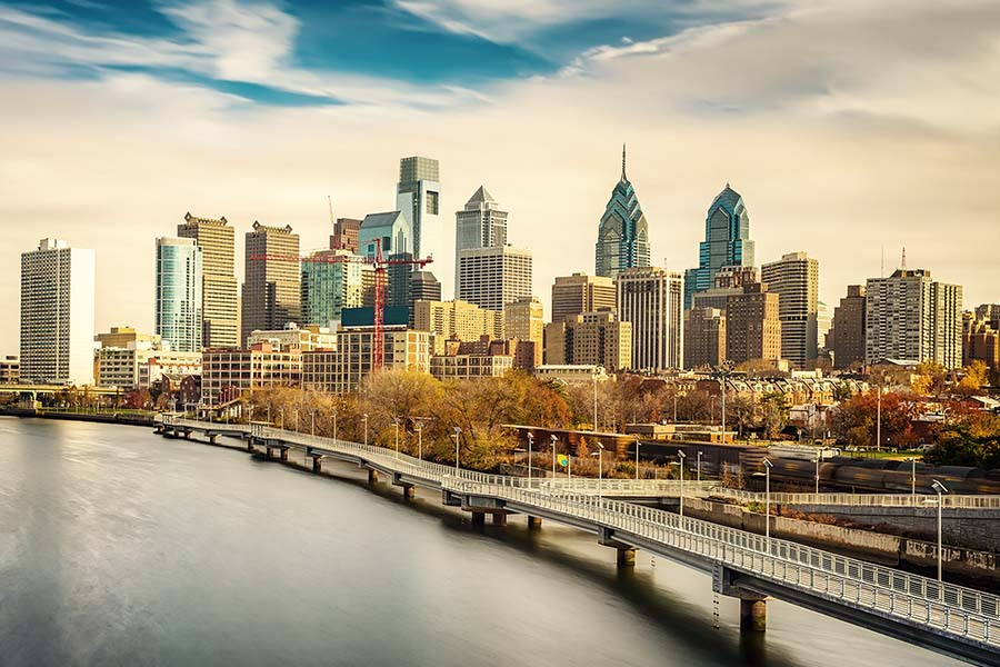 Homepage - View of Philadelphia City Skyline and River Against a Cloudy Blue Sky