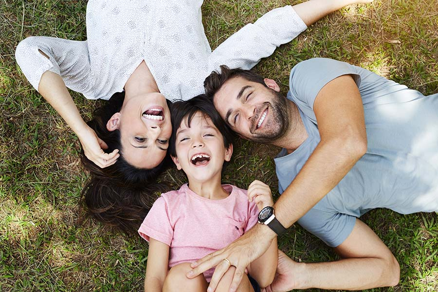 Personal Insurance - Portrait of a Smiling Family with a Young Boy Having Fun Playing in the Park