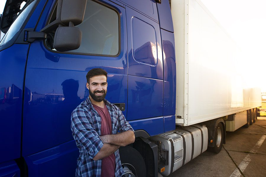 Specialized Business Insurance - Portrait of a Young Smiling Truck Driver Standing Next to His Blue Truck in a Parking Lot