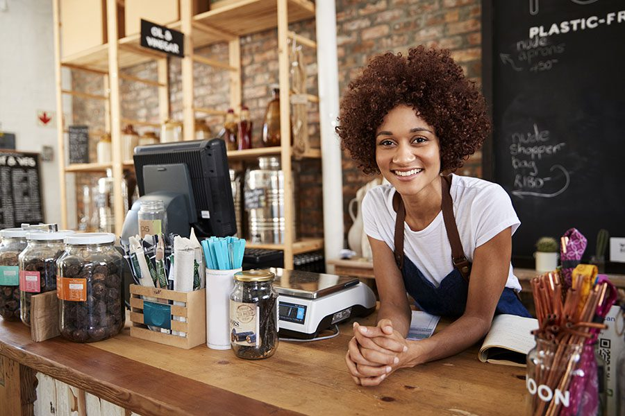 Business Insurance - Closeup View of Happy Young Business Owner Standing Behind the Counter in Her Coffee Shop