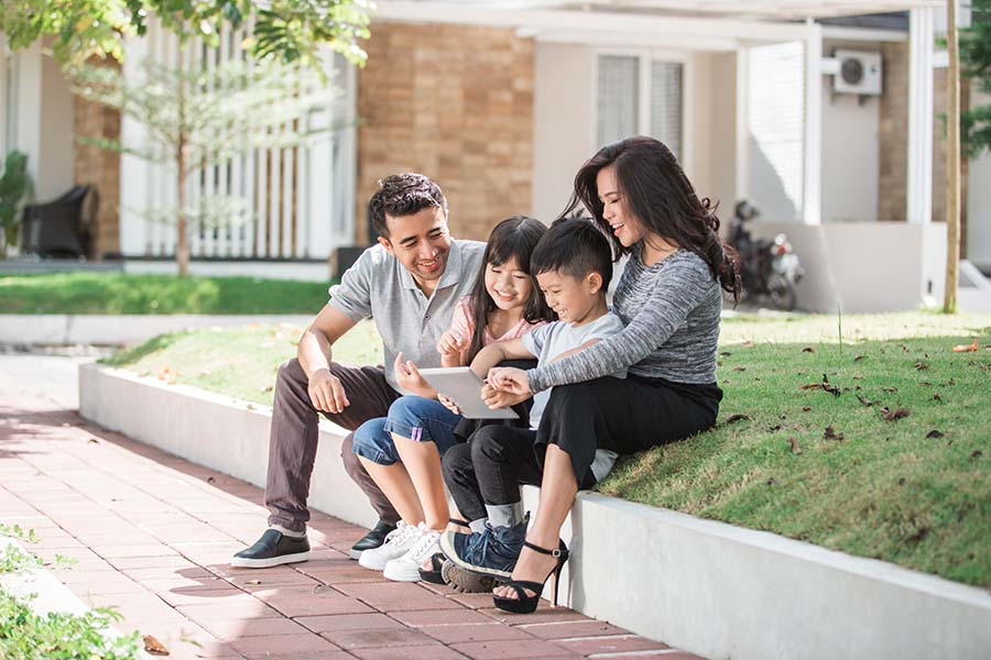 Client Center - View of a Happy Family with Two Kids Sitting on the Grass in Front of Their Home Using a Tablet
