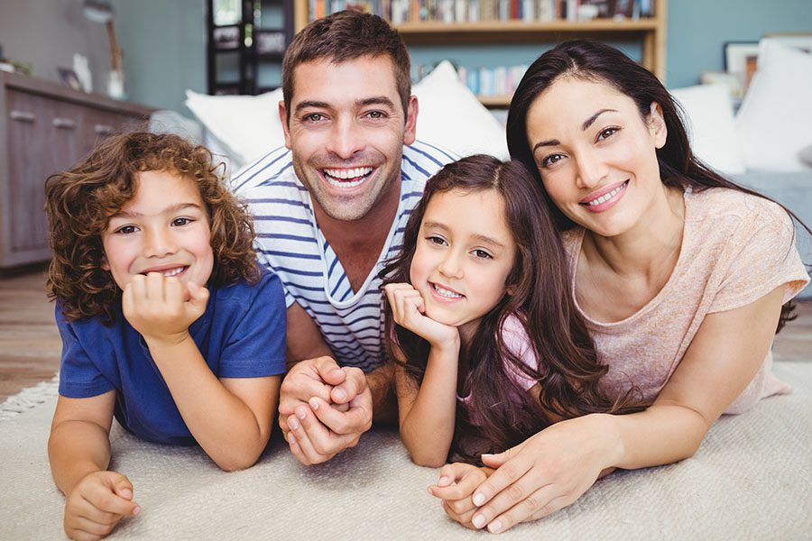 Personal Insurance - Portrait of Smiling Family with Two Kids Laying on the Rug in the Living Room