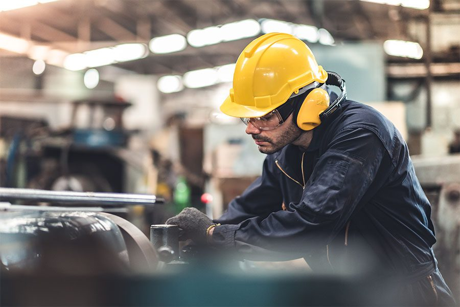 Specialized Business Insurance - Closeup View of Worker in the Factory Working on the Manufacturing of New Equipment