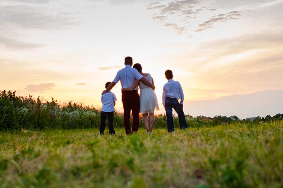 About Our Agency - Family Stands in a Green Field With Their Arms Around One Another, Watching a Golden Sunset