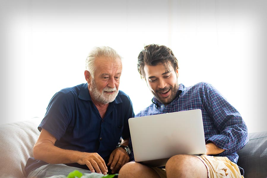 Client Center - Man and His Father Use a Computer While Sitting on a Couch Together