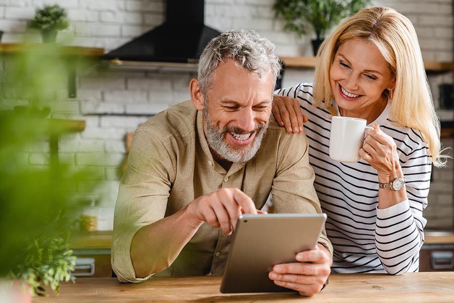 Contact Us - Couple Uses a Tablet at Their Kitchen Island While Enjoying Coffee, Smiling