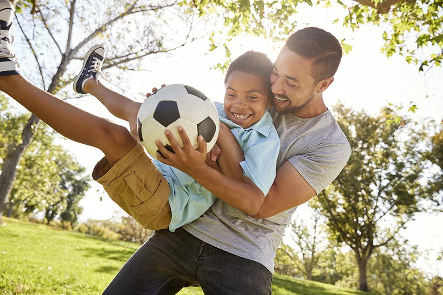Personal Insurance - Father Scoops up His Son as They Laugh and Play Soccer in Their Large Back Yard With Trees and Blue Sky Overhead