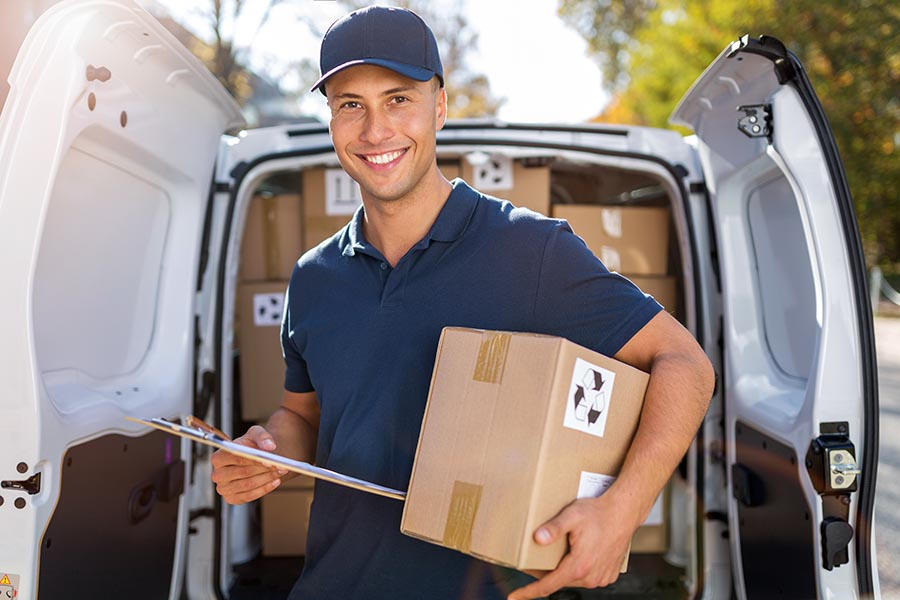 Business Insurance - Man in Blue Uniform Holds a Package and Clipboard in Front of Open Delivery Truck