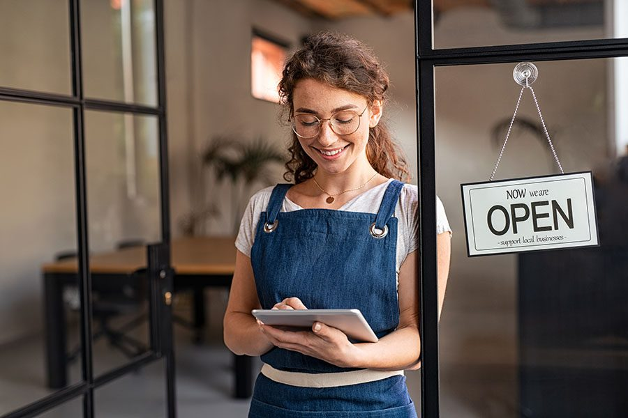 Business Insurance - Closeup Portrait of a Smilng Business Owner Using a Tablet While Standing Next to the Front Door of Her Store with an Open Sign