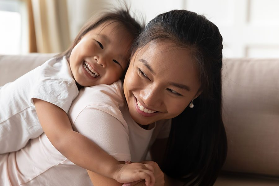 Client Center - Smiling Young Mom Playing with Her Happy Young Daughter at Home