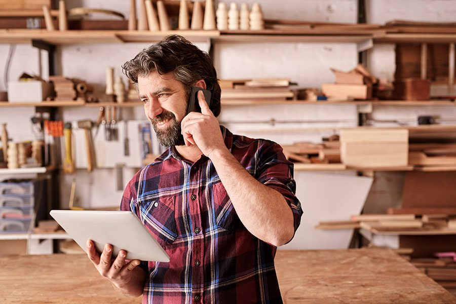 Contact - View of Smiling Business Owner Standing in His Woodworking Shop While Using a Tablet and Making a Call on His Phone