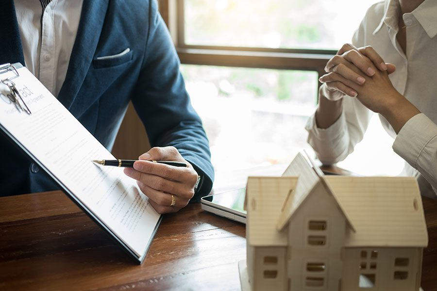 Specialized Business Insurance - Closeup View of Property Manager Showing a Clipboard with Documents to a Business Partner in the Office with a Wooden Home Model Sitting on the Table