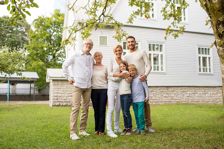 Personal Insurance - Cheerful Extended Family Standing Outside Their Home on the Green Grass