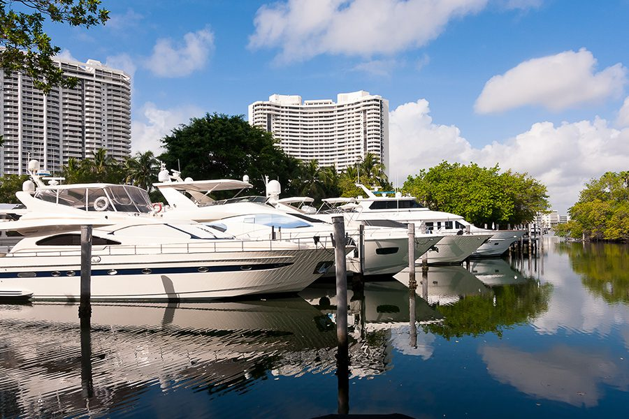Aventura, FL - Yachts in a Marina in Aventura, Florida on a Birght Sunny Day with Resort Hotel Buildings in the Background