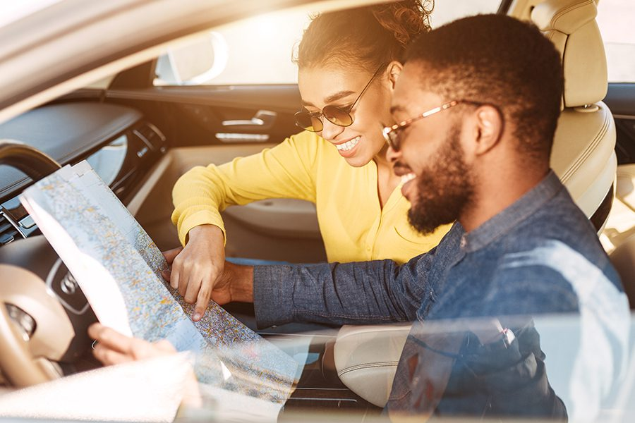 Personal Insurance - Closeup of Young Couple Looking Over Map in Car and Getting Ready to Take a Road Trip in New Vehicle