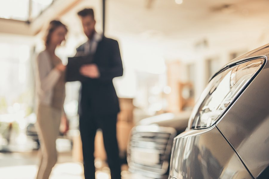Specialized Business Insurance - Blurred View of Dealership and Car Salesman Having Customer Sign Lease Agreement on New Car
