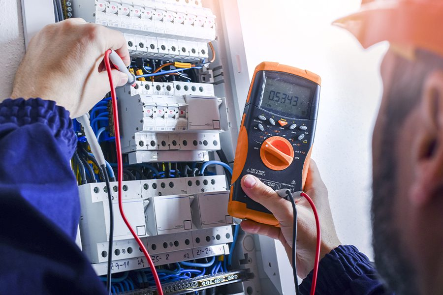 Electrical Contractor Insurance - Electrician Installing Electric Cable Wires in a Fuse Switch Box