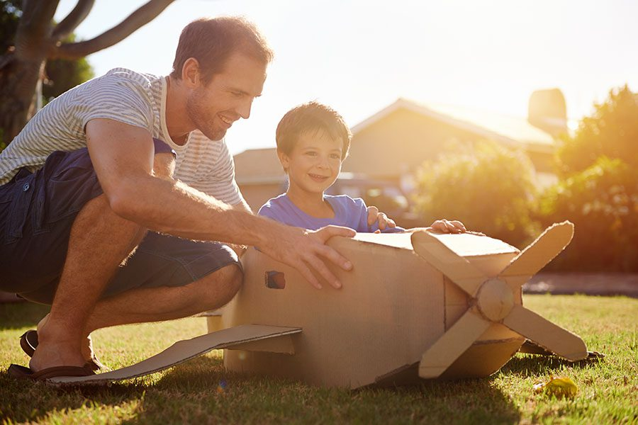 About Our Agency - Smiling Father and Son Playing Outside in the Backyard with a Cardboard Plane on a Warm Summer Afternoon