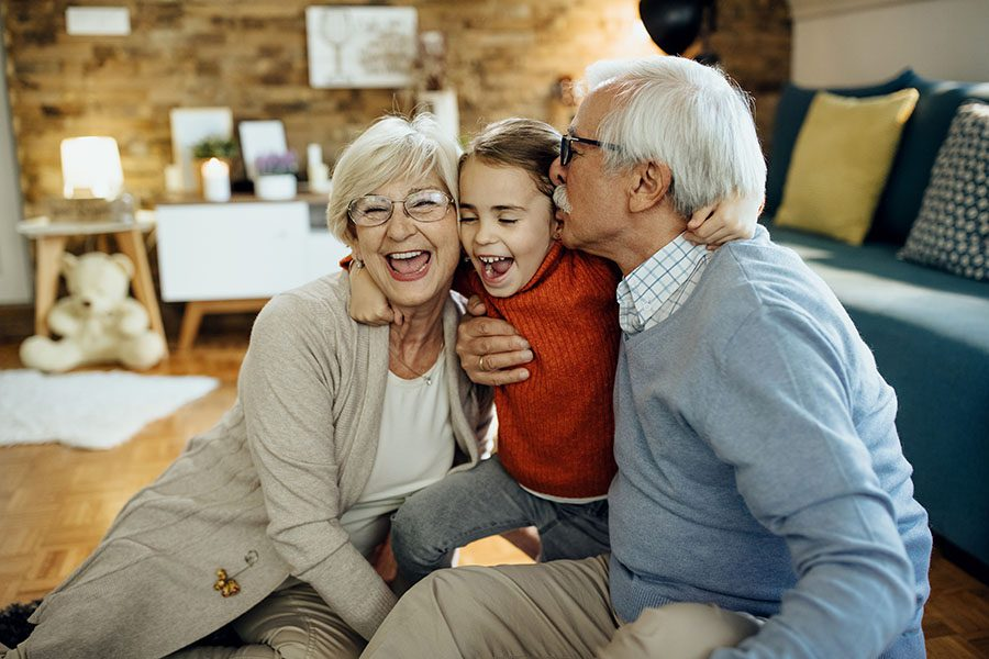 Client Center - Portrait of Cheerful Grandparents Sitting in the Living Room Having Fun Playing with Their Granddaughter