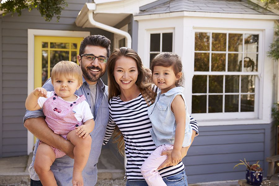 Personal Insurance - Portrait of a Smiling Family with Two Young Daughters Standing Outside Their New Home