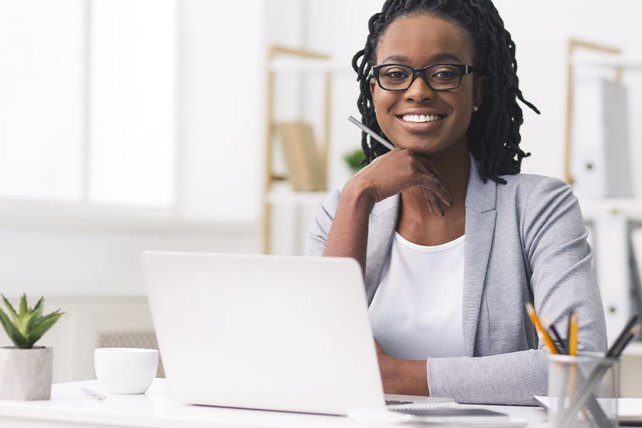 Business Insurance - Portrait of Businesswoman Smiling at Her Desk in the Workplace