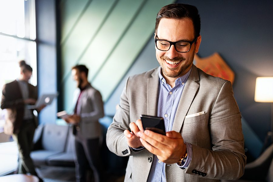 Business Insurance - Businessman Checking Emails on His Phone in Modern Office