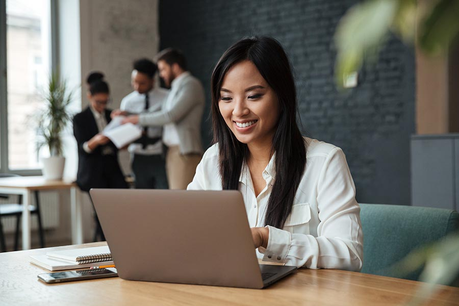 Client Center - Woman Uses Computer in Brick Office, Smiling as Others Work in the Background