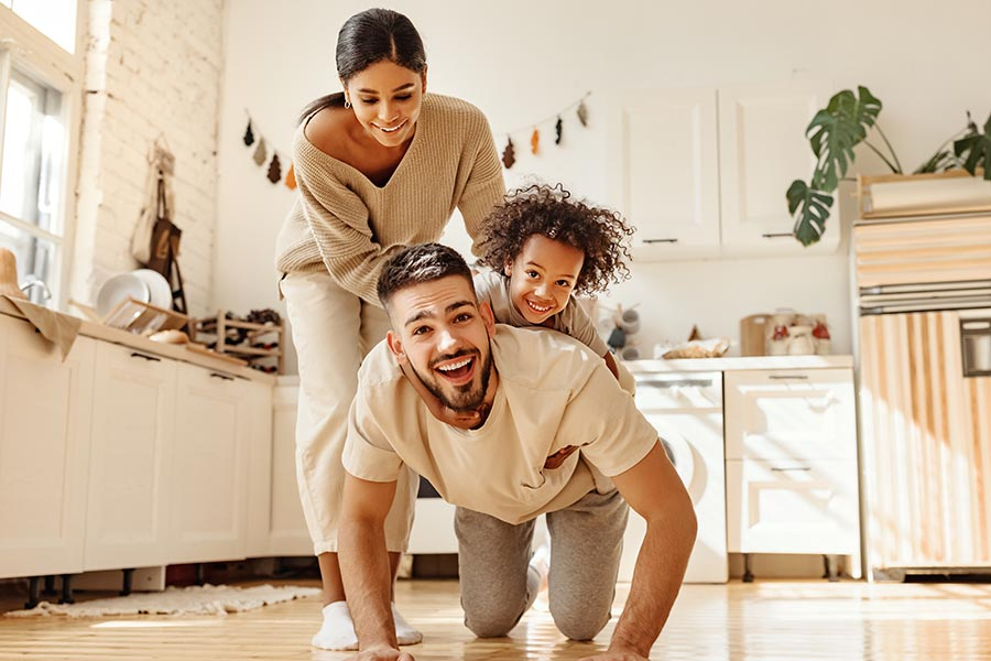 Personal Insurance - Young Family Plays in Their Kitchen, Daughter Riding on Her Dad's Back as Mom Laughs and Helps