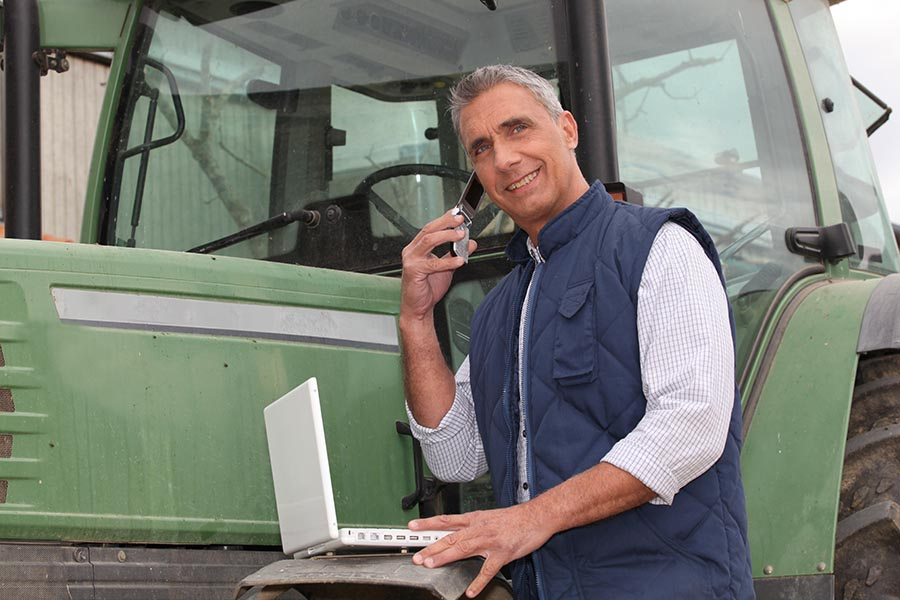 Specialized Business Insurance - Farmer Makes a Call Leaning Against His Green Tractor, Smiling and Wearing a Blue Vest