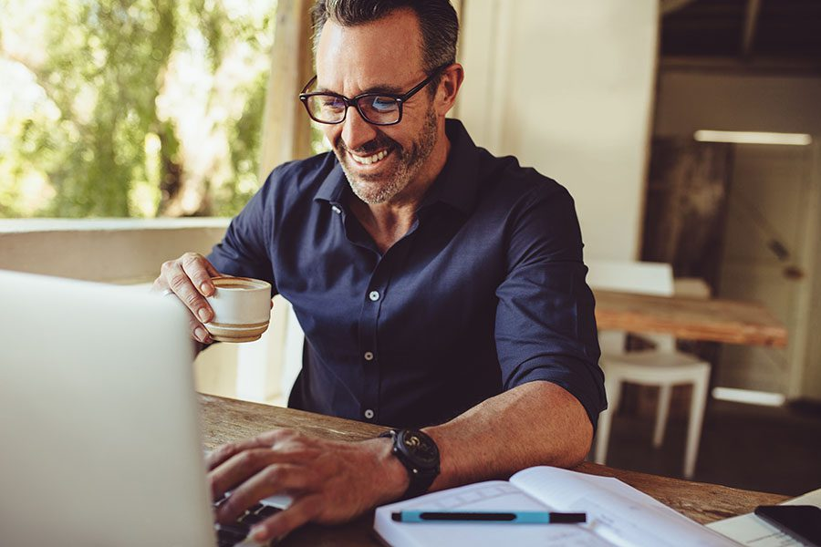 Blog - Mature Businessman Sitting at Home Enjoying a Cup of Coffee and Using His Laptop
