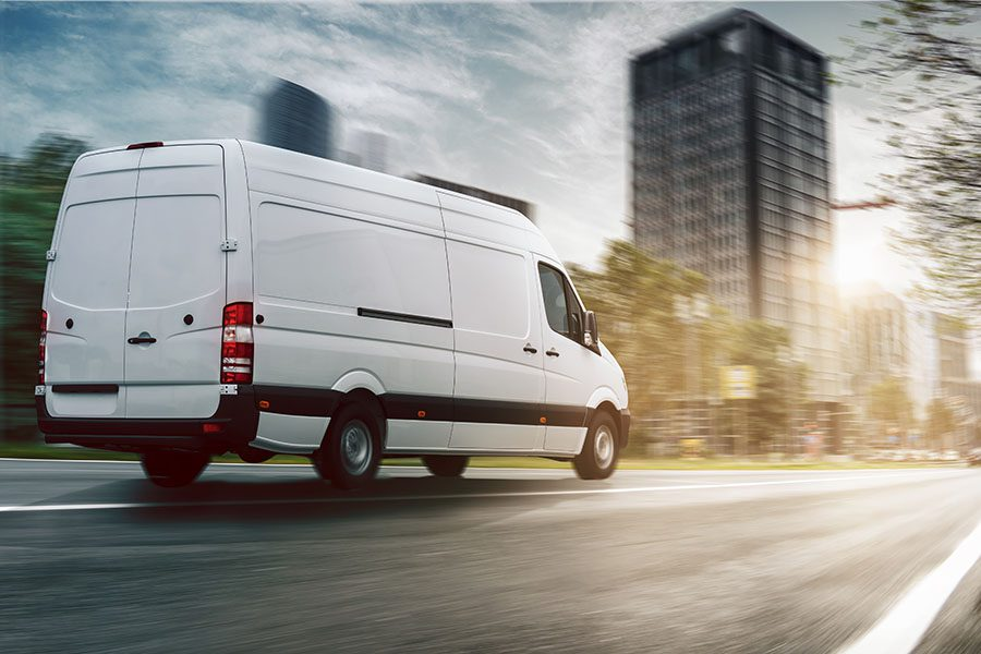 Business Insurance - White Commercial Van Driving Through Business District in a City