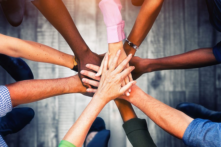 Community Involvement - Diverse Group of People Stacking Their Hands Together Outdoors