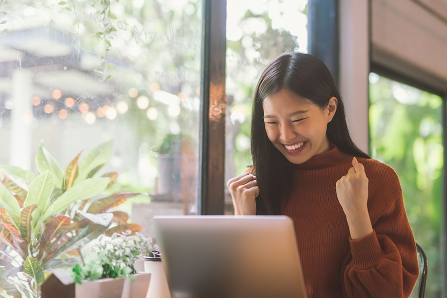 Resources - Excited Woman Sitting at a Cafe Using Her Laptop Celebrating Success