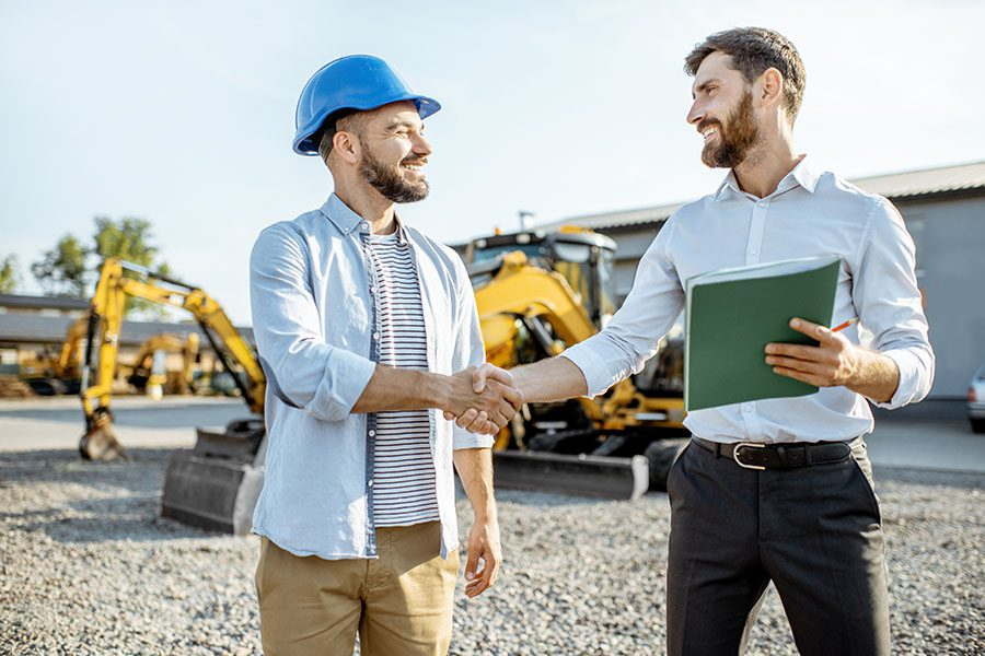Specialized Business Insurance - Smiling Contractor and Businessman Shaking Hands at a Construction Jobsite with Heavy Machinery in the Background