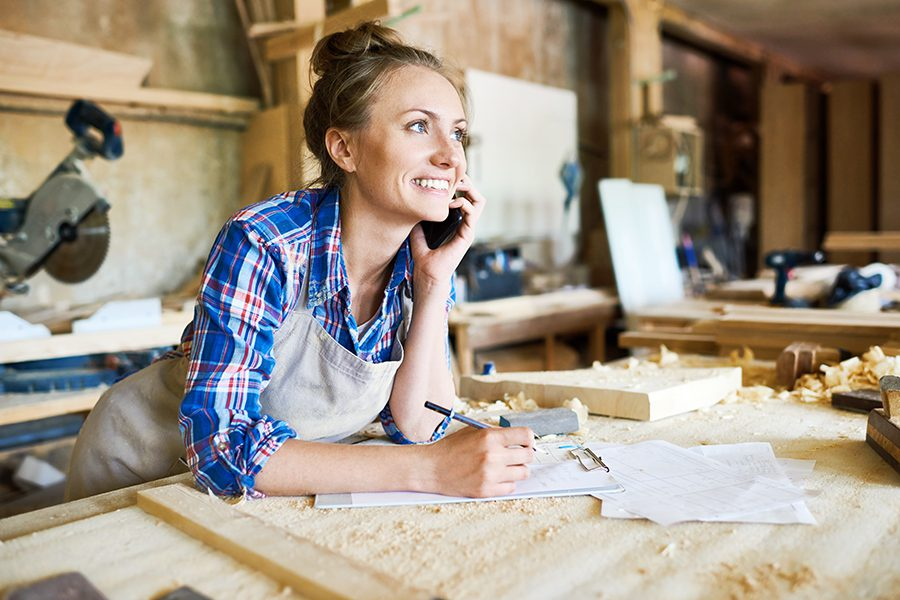 Business Insurance - Cheerful Young Carpenter Discussing Order Details with Her Customer on a Smartphone and Taking Notes