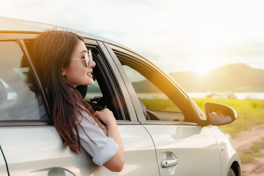 Personal Insurance - Woman with Sunglasses Looking Out Car Passenger Side Window on a Road Trip to a Lake in the Summer