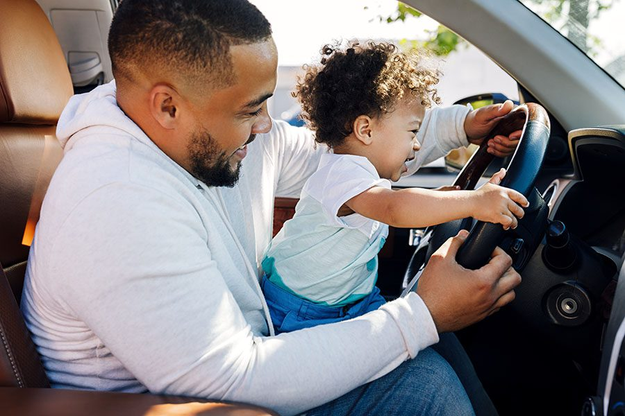 About Our Agency - Closeup View of a Cheerful Father Holding His Son While He Plays with the Steering Wheel in Their Car