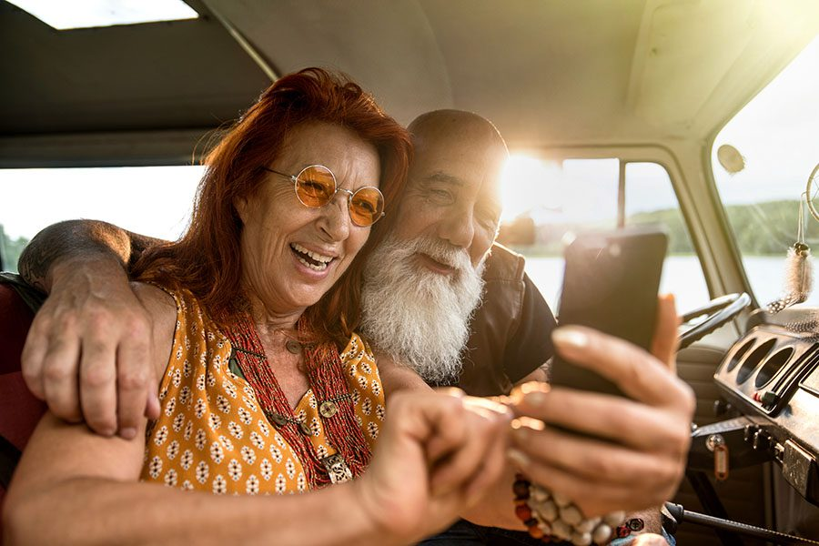 Client Center - Closeup View of a Smiling Older Couple Sitting in Their Van While Using a Phone at Sunset