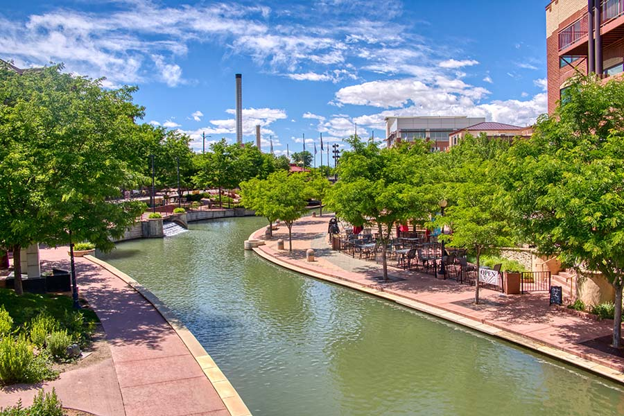 Contact - Scenic View of Downtown Pueblo Colorado with Buildings Surrounded by Green Trees Next to a Winding River on a Sunny Day