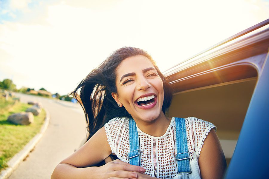 Insurance Quote - Closeup Portrait of a Cheerful Young Woman Sticking Her Head Out the Window While on a Road Trip on a Sunny Day