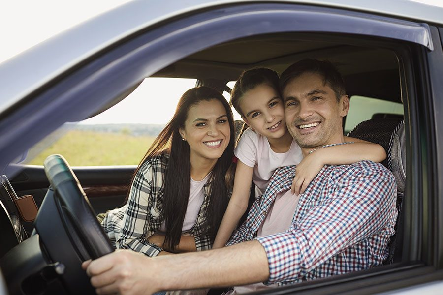 Personal Insurance - Portrait of a Cheerful Family with a Daughter Sitting in the Car Ready to Go on a Road Trip Together