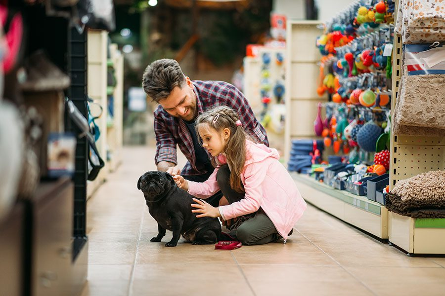 Pet Store Insurance - Father and Daughter in the Pet Store with Their Dog