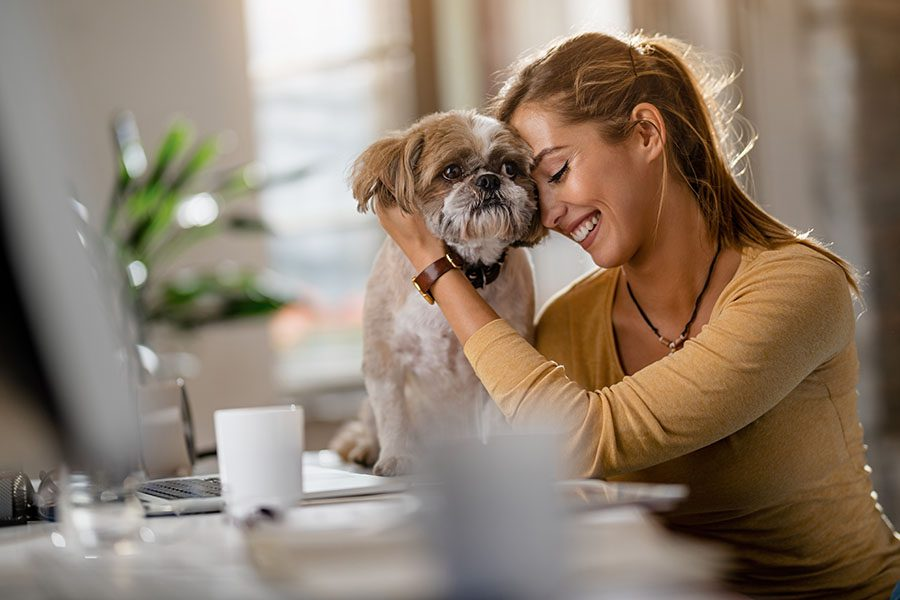 Refer a Pet Business - Closeup View of a Smiling Woman Sitting in Her Office Cuddling with Her Dog
