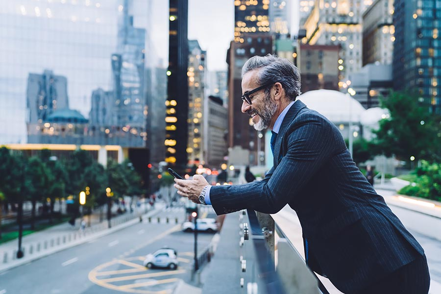Client Center - Businessman Leans Against a Balcony Wall Overlooking a New York City Street, High Rise Buildings Lighting up in the Background