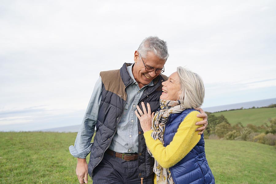 Contact Us - Happy Senior Couple Stands on a Grassy Hill, Arms Around One Another, Dressed for Cold Weather