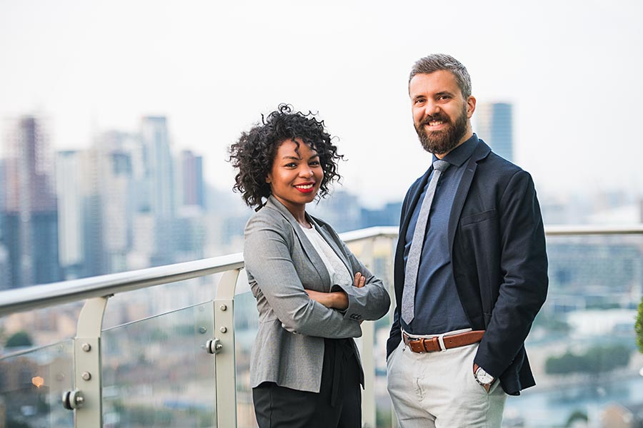 Employee Benefits - Two Smiling Coworkers Stand on a Balcony on a High Rise Office Building