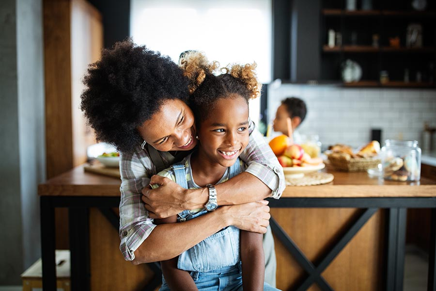 Personal Insurance - Mother Hugs Her Smiling Young Daughter From Behind in Their Kitchen