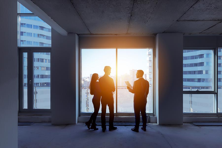Specialized Business Insurance - Property Manager Shows a Couple a New Building Under Construction