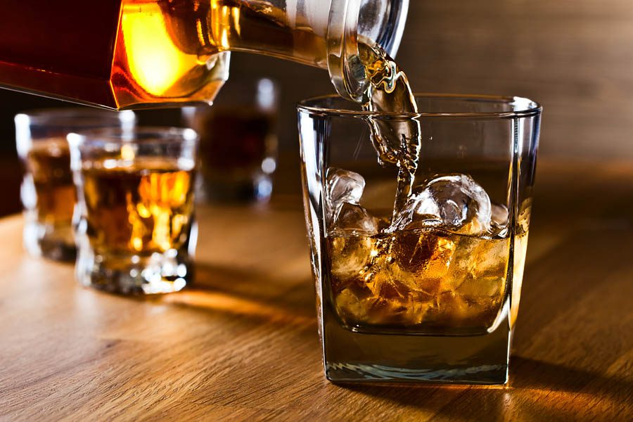 Distillery Insurance - Pouring Whiskey Into a Bar Glass with Fancy Ice Cubes