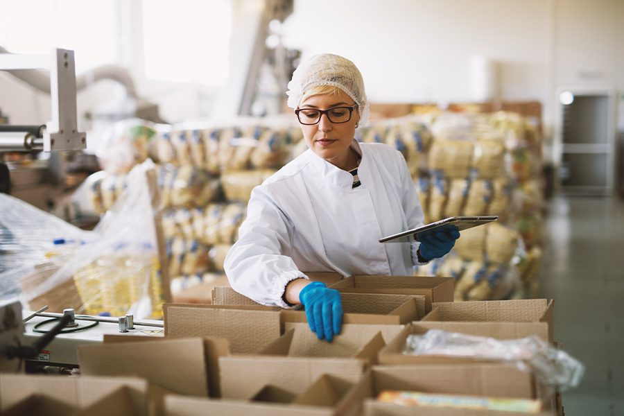 Food Distributors Insurance - Employee in Sterile Clothes Checking Food Packages Ready to be Delivered